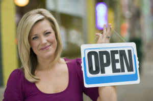 woman holding sign that says open for business
